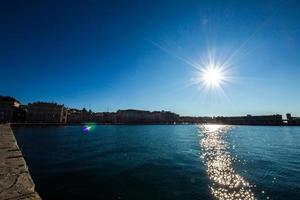zon op zee voor piazza unità trieste foto