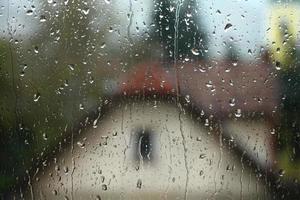 regendruppels op venster met huis en kerk op achtergrond foto