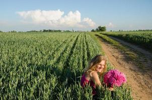 lange landelijke pad en vrouw zit met pioenroos bloem foto