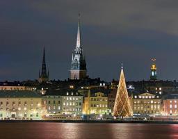 skyline bij nacht in stockholm met verlichte kerstboom