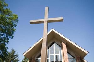 brede hoek van hoog kruis met moderne kerk op achtergrond