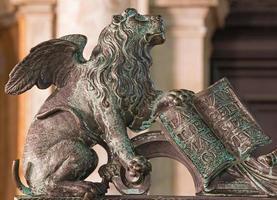 venetië - leeuw bronzen standbeeld van poort van klokkentoren. foto