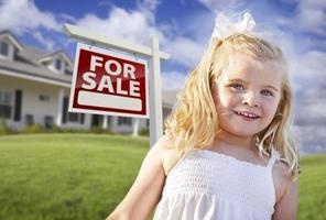 meisje in tuin met onroerend goed te koop bord, huis foto
