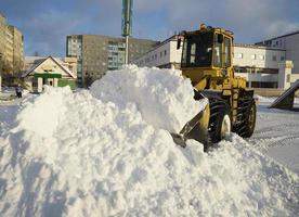 tractor schop sneeuw in stapel op straat.