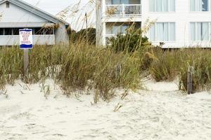 Blijf alsjeblieft weg van het bord met duinen en strandhuisjes foto