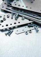 metalen voorbereidingen en bevestigingselementen op de gekraste metalen achtergrond foto