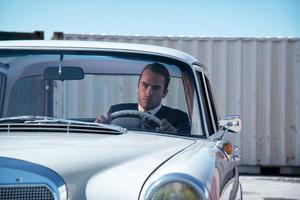 retro mode man met grijs pak zitten in klassieke auto.