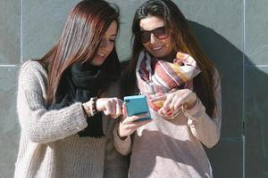jonge meisjes en vrienden staan met behulp van een smartphone foto
