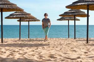 tiener in de buurt van parasols op het strand foto