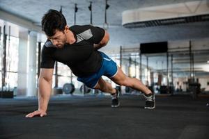 atleet doet push-ups met één hand foto