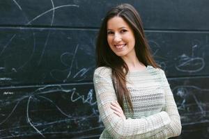 jonge mooie vrouw stond voor een schoolbord muur. foto