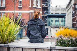 jonge vrouw sittin gon bank in de stad