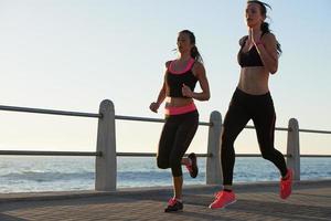 twee vrouwelijke atleten die buitenshuis fitness tracker-apparaat uitvoeren