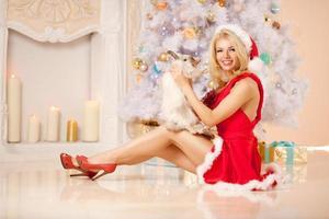 jonge mooie lachende santa vrouw in de buurt van de kerstboom met foto