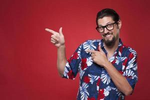gelukkige jonge man in hawaiiaans overhemd zijwaarts wijzend