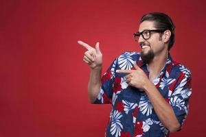 gelukkige jonge man in hawaiiaans overhemd zijwaarts wijzend foto