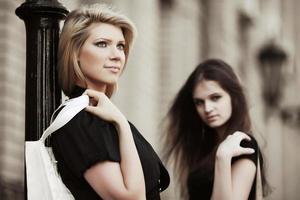 twee gelukkige jonge vrouwen op de stadsstraat foto
