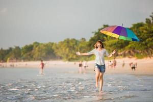 vrolijk jong meisje met regenboogparaplu die pret heeft op foto