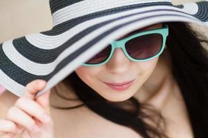jonge brunette in turqoise zonnebril