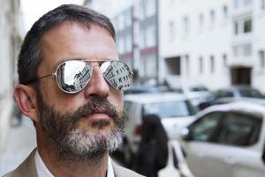 man in pak met zonnebril in de straat foto