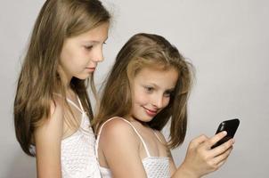 twee jonge meisjes die een selfie met de mobiele telefoon nemen. foto
