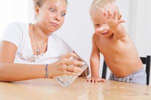 oudere zus speelt met haar broertje met water foto