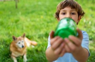 schattige jongen drinken uit de fles, hond kijken op de achtergrond foto