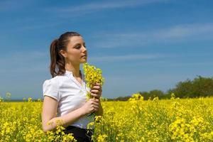 meisje met gele bloemen in het veld foto