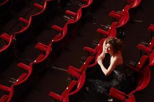 gelukkige vrouw zitten in theater kraam foto