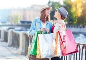 twee gelukkige mooie meisjes met boodschappentassen in de stad foto