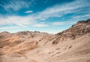 bruine heuvels onder bewolkte blauwe hemel foto