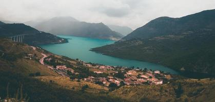 luchtfoto van huizen en bergen naast meer