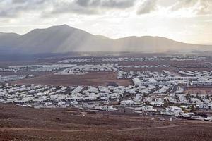 uitzicht over playa blanca in ochtendlicht met bergen foto