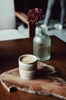 koffiemok op bruine houten plaat met bloemenvaas