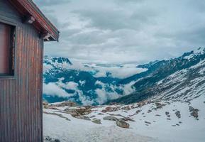 bruine schuur op met sneeuw bedekte berg foto