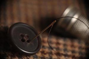 naaien knoop op een tweed jas