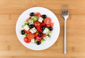 glazen plaat met Griekse salade en vork op bamboe tafel foto