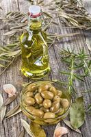 olijven in kom en olijfolie foto