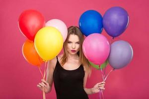 aantrekkelijke flirterige vrouw met kleurrijke ballonnen die verrassing plannen foto