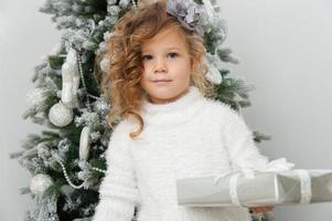 schattig kind meisje met cadeau in de buurt van kerstboom foto