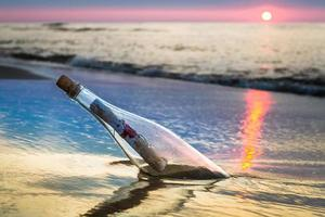 fles met een bericht dat door de zee wordt gegooid foto