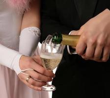 de twee handen met een fles champagne foto