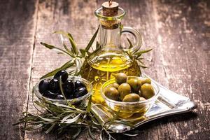 olijfolie en olijven op houten tafel foto