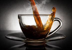 giet koffie in een doorzichtige glazen beker met donkere achtergrond. foto