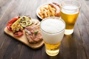 bier in glas met gastronomische biefstuk en frietjes foto