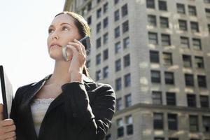 zakenvrouw met behulp van mobiele telefoon tegen gebouw foto