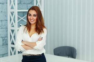 jonge mooie zakenvrouw permanent met gevouwen armen foto