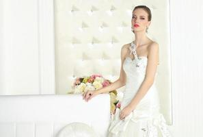 prachtige bruid in een witte kamer, poseren foto