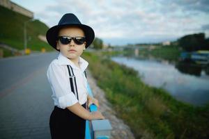 kleine heer met zonnebril buitenshuis foto