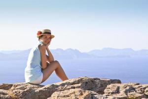 jonge vrouw zittend op de rotsen naast de zee foto